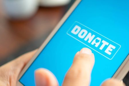 Photo of person using mobile phone to donate to charity